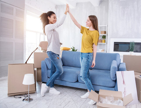 two-roommates-high-fiving-in-their-new-apartment